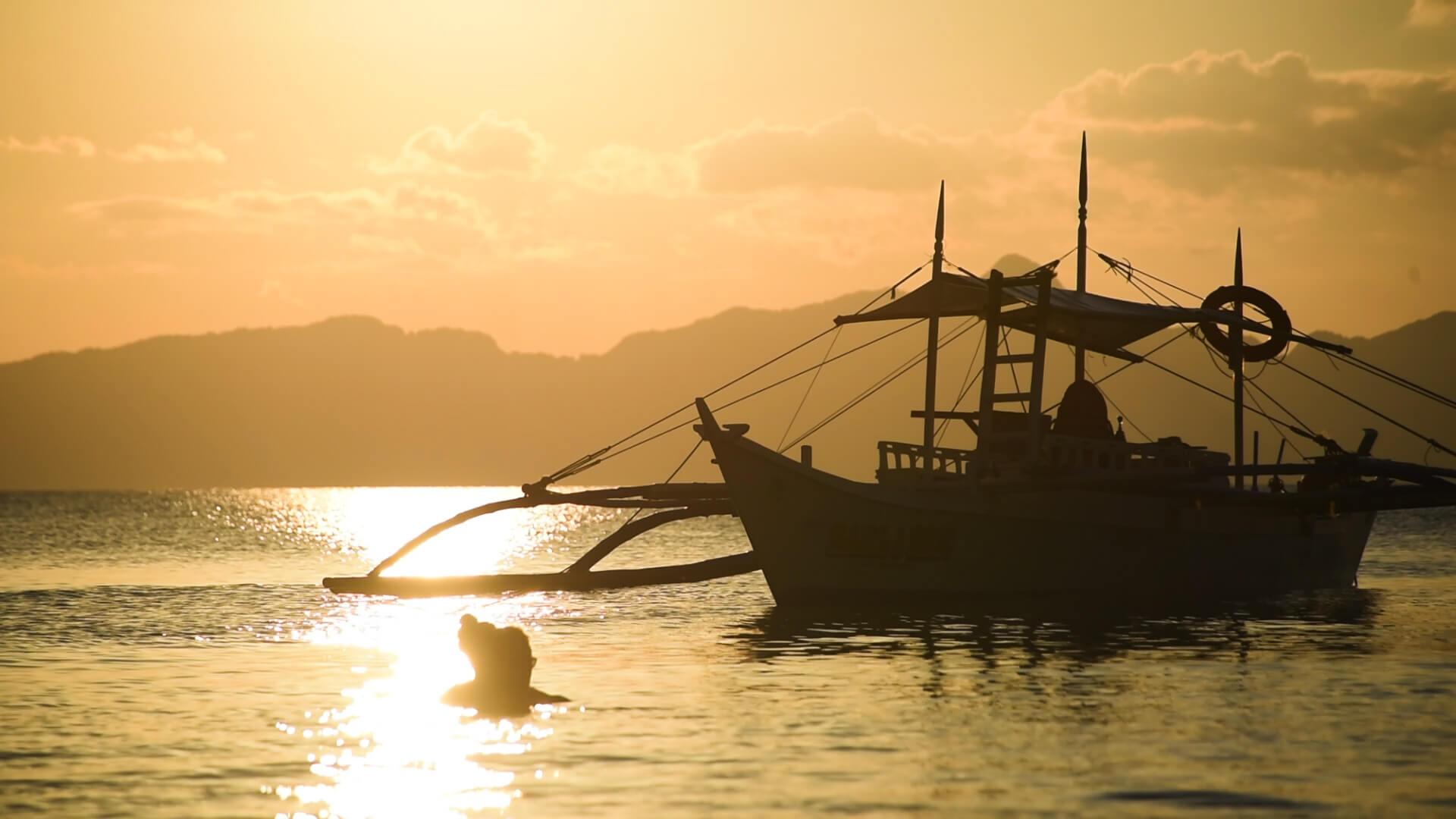 夕日と欧米人カップルとバンカーボートの写真