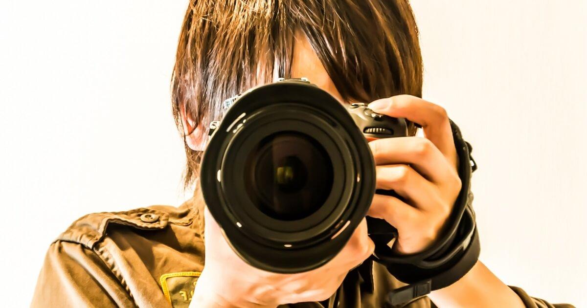 一眼レフを構えたカメラマンの画像